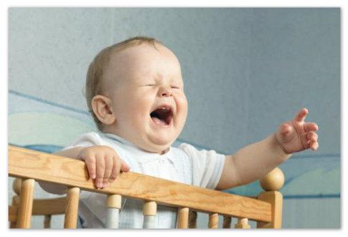 Плачущий ребенок в кроватке
