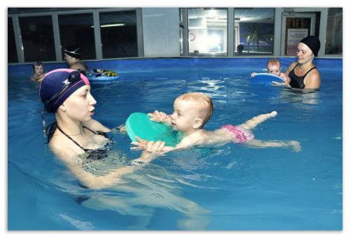 Ребенок плавает с дощечкой.