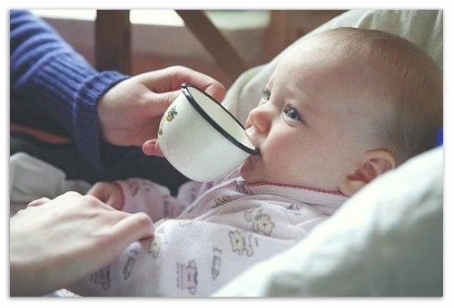 Ребенок пьет из кружки.