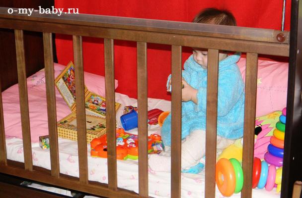 Малыш с удовольствием играет в кроватке.