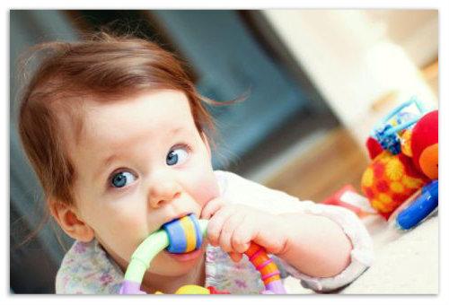 Ребенок грызет игрушку.