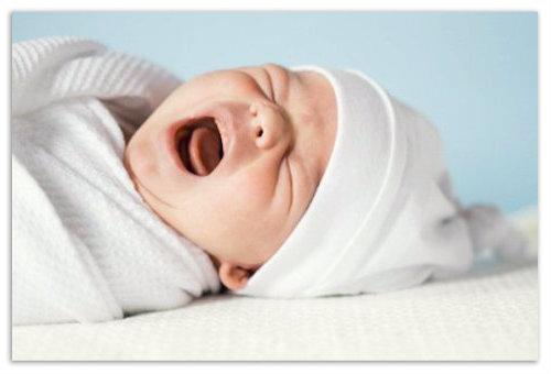 Ребенок лежит и плачет.