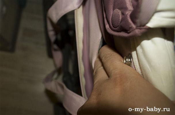 Лезем в кармашек, нажимает там на кнопку, люлька отстёгивается.