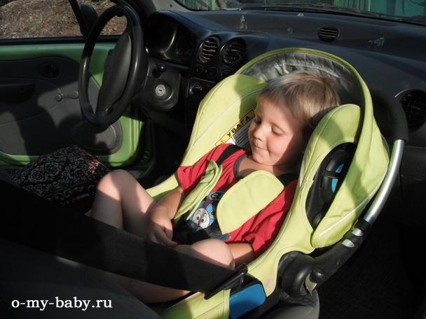 Взрослый мальчик залез в автокресло.