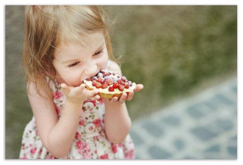 Девочка ест пирожное.