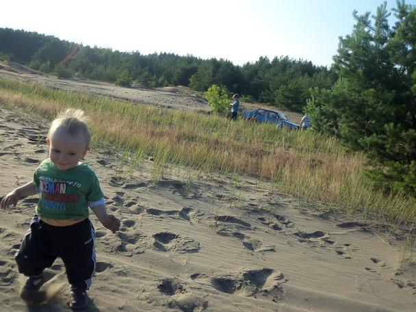 Маленький мальчик идёт по песку.