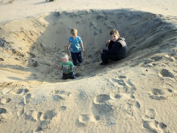 Мальчишки сидят в яме.