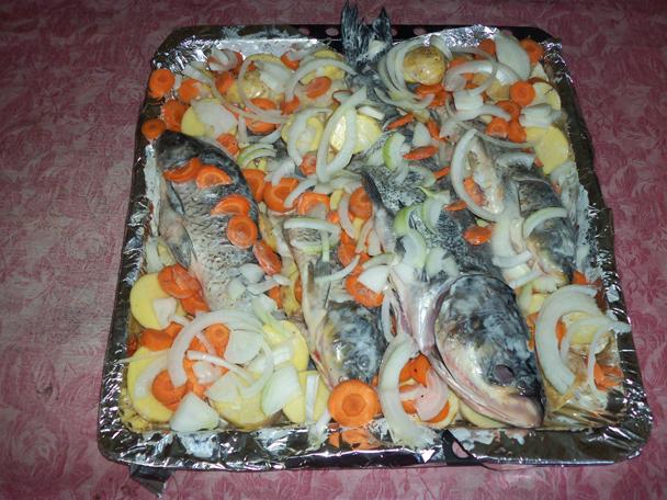 Карп с картошкой морковью и луком на противне.