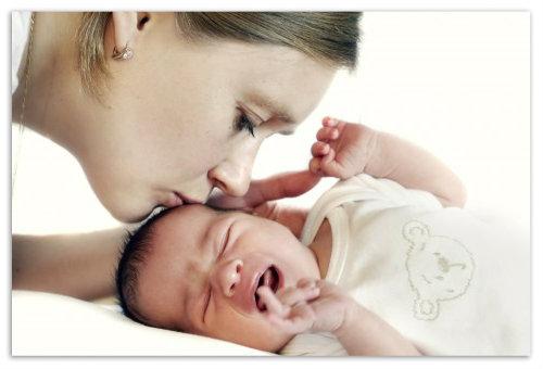 Целует плачущего младенца.