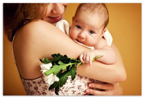На руках у мамы с цветком.