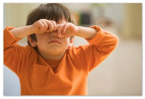 Мальчик трет глаза