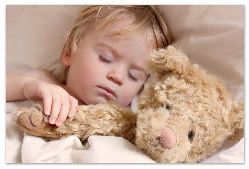 Девочка спит с мишкой.