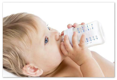 Ребёнок пьёт из бутылочки.