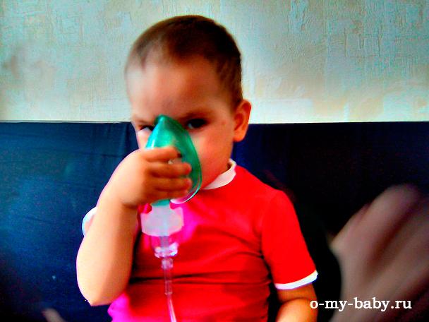 Ребёнок держит маску.