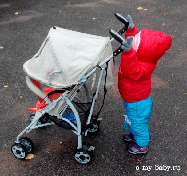 Малыш катает коляску.