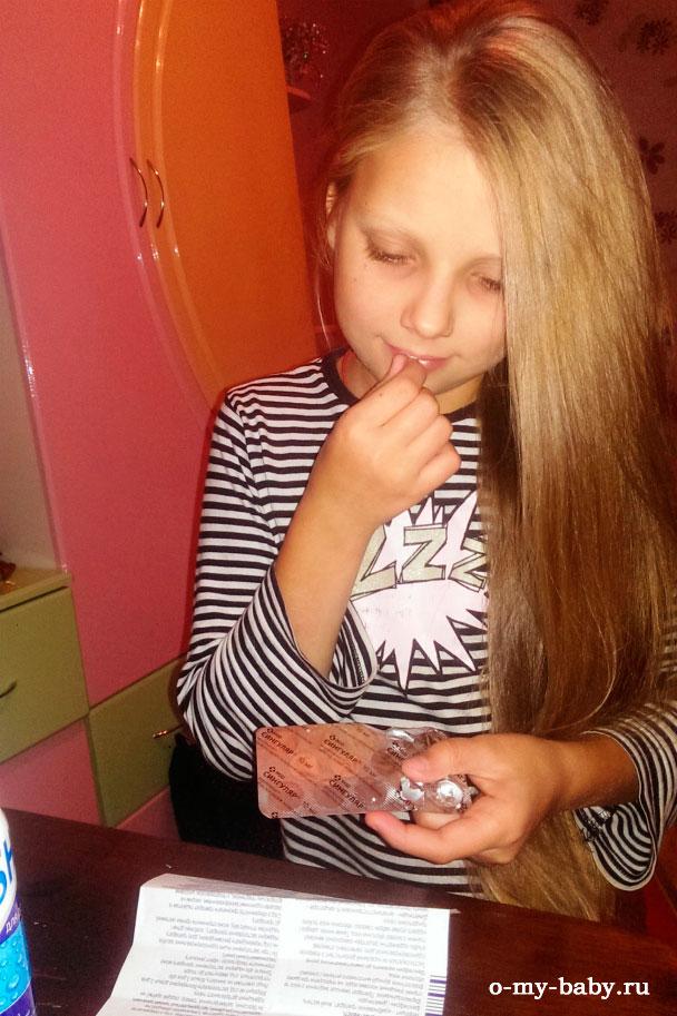 Девочка пьёт таблетки.